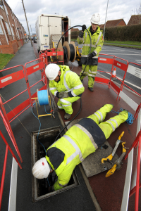 Telephone engineers laying cable